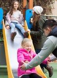 Os pais com duas filhas descansam na terra para crianças Imagens de Stock Royalty Free