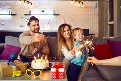 Os pais com um bolo felicitam sua criança em seu aniversário fotos de stock