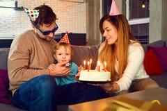 Os pais com um bolo felicitam sua criança em seu aniversário foto de stock