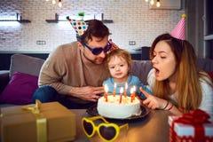 Os pais com um bolo felicitam sua criança em seu aniversário foto de stock royalty free