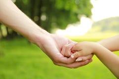 Os pais da família guardam a mão de uma criança pequena fotografia de stock