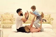 Os pais da licença da puericultura com caras felizes pagam a atenção à criança, jogam, aplaudem as mãos Mãe e pai que afagam com  fotografia de stock royalty free