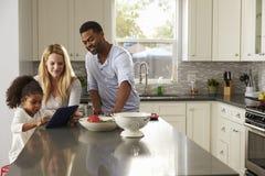 Os pais da menina e da raça misturada usam o tablet pc na cozinha fotografia de stock
