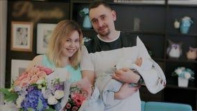 Os pais de sorriso felizes novos aceitam felicitações e levantamento para uma foto com bebê recém-nascido Mãe nova com flores vídeos de arquivo