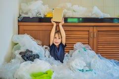 Os pais do menino usaram sacos de pl?stico demais que encheram acima a cozinha inteira O menino mostra-lhes um saco de papel zero imagem de stock