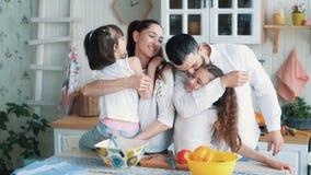 Os pais e as duas filhas que cozinham na cozinha, abraçam e riem, movimento lento