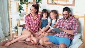 Os pais e duas filhas encontram-se na cama e o paizinho l?-lhes o livro, movimento lento filme
