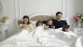 Os pais e seus filha e filho estão usando os dispositivos que encontram-se em uma cama branca Retrato da família moderna durante  filme