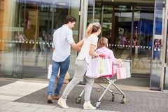 Os pais empurram crianças no carrinho de compras foto de stock