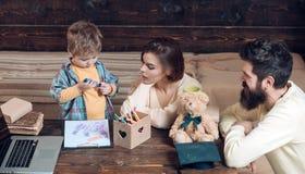Os pais ensinam o filho, fundo de madeira da parede Menino que escuta a mamã e o paizinho com atenção Conceito de Homeschooling p imagem de stock