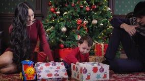 Os pais estão felizes olhar como os seus filho desembalam seu presente do Natal Morena bonita com o cabelo longo que fala com ela vídeos de arquivo