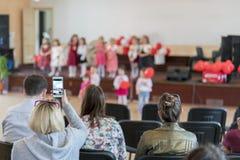 os pais estão olhando as crianças do desempenho no jardim de infância Um feriado das crianças no jardim de infância Discurso das  fotos de stock royalty free