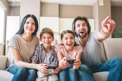 Os pais estão sentando-se junto com suas crianças no sofá As crianças jogam o jogo no playstation O indivíduo está apontando para imagem de stock