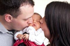 Os pais felizes beijam seu recém-nascido Imagem de Stock Royalty Free