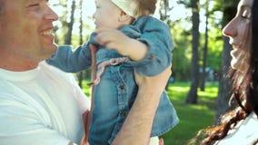 Os pais felizes guardam e beijam sua filha pequena fora com alargamento da lente vídeos de arquivo