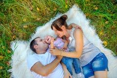 Os pais felizes jogam com a criança que encontra-se em uma grama imagem de stock royalty free