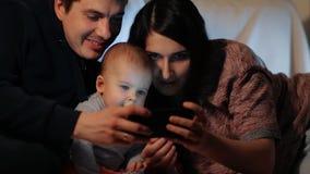 Os pais felizes novos e seu filho pequeno olham a tela e o sorriso do smartphone Tiro do movimento lento video estoque