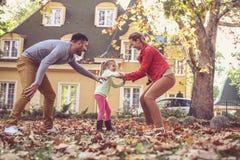 Os pais felizes têm o jogo com filha No movimento Foto de Stock Royalty Free