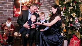 Os pais jogam com crianças, véspera feliz do ` s do ano novo da família, retrato de uma família feliz, mãe, pai e filhos comemora vídeos de arquivo