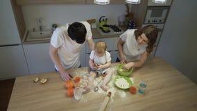 Os pais junto com uma filha pequena estão cozinhando na cozinha em casa O conceito da felicidade da família filme