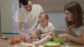 Os pais junto com uma filha pequena est?o cozinhando na cozinha em casa O conceito da felicidade da fam?lia vídeos de arquivo