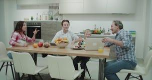 Os pais maduros com suas crianças que passam o tempo na tabela de jantar que olham algo no paizinho do portátil shoo algum vídeos de arquivo