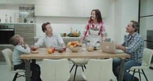 Os pais maduros da família atrativa na manhã que toma um café da manhã saudável junto na cozinha, paizinho têm seu portátil video estoque