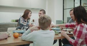 Os pais maduros e suas crianças têm-nos um jantar caseiro junto, muito com fome comendo o alimento e sentindo o soo video estoque