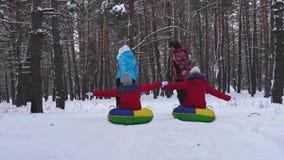 Os pais montam crianças em pires da neve no parque da neve do inverno Mamã e filhas do paizinho que jogam por feriados do Natal vídeos de arquivo