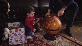 Os pais mostram seu globo pequeno do filho a que toca em sua mão Infância feliz de um rapaz pequeno Perto do menino é filme