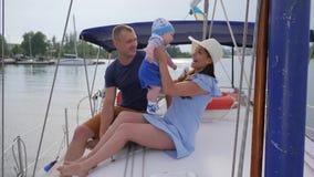Os pais novos com o rapaz pequeno no rio, feriado do curso de pares felizes com o bebê na navigação yacht no mar, filme