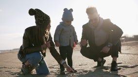 Os pais novos com seu menino da criança da criança que joga com a areia no tempo ventoso, no homem e na mulher nebulosos frios aj filme
