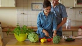 Os pais novos e sua filha pequena cozinham o jantar junto na cozinha Jantar da família Assistente do ` s da mamã Um feliz video estoque