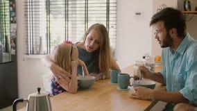 Os pais novos estão tendo o café da manhã com sua filha pequena na mesa de cozinha na manhã Tiro lento do mo Steadicam filme