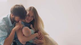 Os pais novos felizes bonitos sorriem a sua mãe recém-nascida preciosa do filho que tranquiliza seu bebê em uma cadeira de balanç foto de stock
