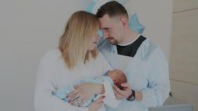 Os pais novos felizes com bebê recém-nascido tocarem em suas testas e apreciarem o momento quando sono do bebê video estoque