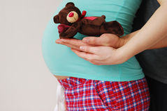 Os pais novos felizes mostram o brinquedo de seu bebê futuro fotos de stock