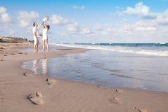Os pais novos jogam com o bebê na praia Fotos de Stock Royalty Free