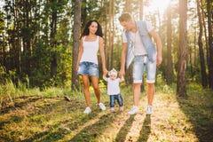 Os pais novos s?o ensinados andar uma filha de um ano na natureza em um parque em um gramado As primeiras etapas da m?o da crian? fotos de stock royalty free
