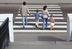 Os pais prendem a mão das crianças e da estrada do cruzamento Fotografia de Stock Royalty Free