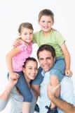 Os pais que dão suas crianças rebocam o passeio que sorriem na câmera Fotos de Stock