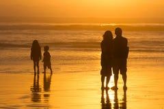 Os pais que olham crianças jogam as silhuetas, por do sol na praia Fotografia de Stock Royalty Free