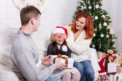 Os pais surpreendem sua filha com caixa de presente fotografia de stock