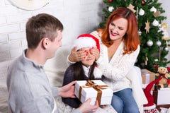 Os pais surpreendem sua filha com presente de Natal fotografia de stock royalty free