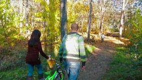 Os pais tomam a bicicleta de uma criança no movimento lento da floresta vídeos de arquivo