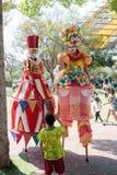 Os palhaços em pernas de pau cumprimentam um visitante pequeno ao parque das atrações Fotografia de Stock