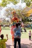 Os palhaços em pernas de pau cumprimentam um visitante pequeno ao parque das atrações Imagens de Stock Royalty Free