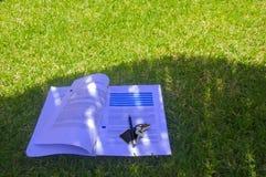 Os papéis com os lections a estudar, escrevem e chaves na grama fotos de stock royalty free