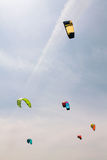 Os papagaios coloridos voam no céu nebuloso Kitesurfing Fotos de Stock Royalty Free