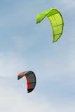 Os papagaios coloridos voam no céu nebuloso Kitesurfing Fotografia de Stock Royalty Free